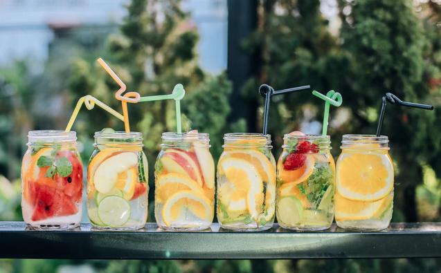 Foto de diversos copos com águas saborizadas com frutas.